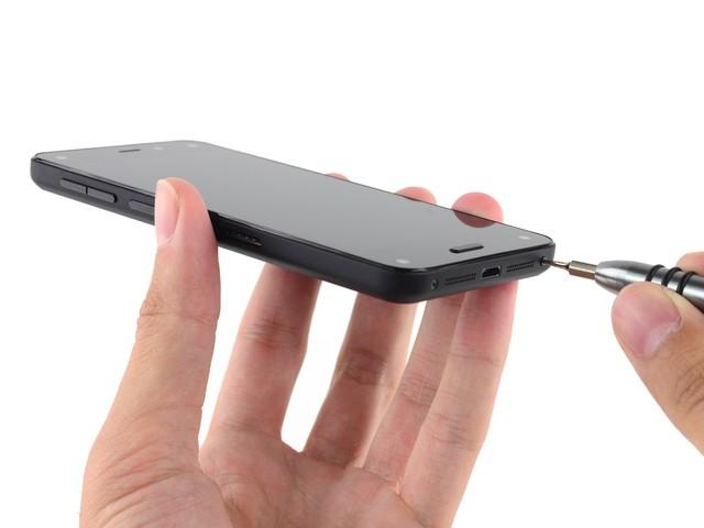 Fire Phone的底部设计有点类似iPhone,因此打开方式也与之相似,首先拧开扬声器两侧的螺丝,然后用吸盘将屏幕打开。